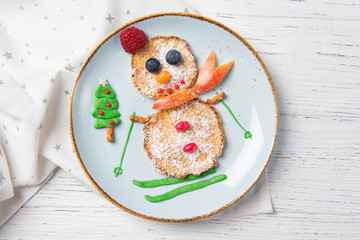 Pancakes in the shape of snowman on ski, Christmas breakfast for kids idea, top view
