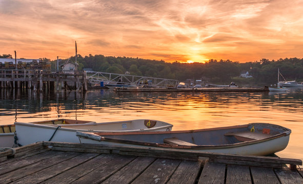 Early morning summer sunrise over calm water and john boats near a working lobster wharf in Muscongus Bay, Maine