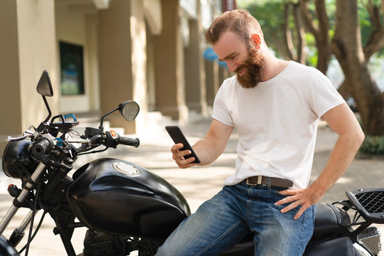 Cheerful motorbike rider having video call. Young man with bushy beard sitting on motorcycle and smiling at phone screen. Communication concept