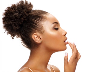 Beautiful woman in profile touching her lips. Photo of african woman finishes makeup on white background. Youth and skin care concept