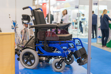 Wheelchair at a medical exhibition. Wheelchair with electric motor Wall mural