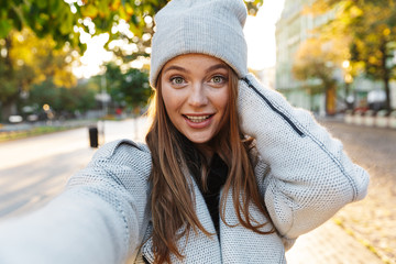 Beautiful young woman dressed in autumn coat and hat