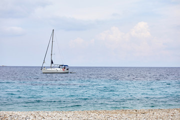 Sailing yacht in the Mediterranean. Concept of travel and active lifestyle. Stone beach and warm sea