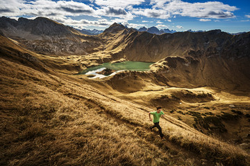 Germany, Allgaeu Alps, man running on mountain trail
