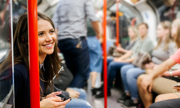 UK, London, portrait of smiling woman with cell phone sitting in underground train