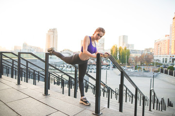 Street portrait of a girl who is sweeping through the track by the background of a city landscape, looks at the camera. Fitness girl doing stretching outdoors in front of running. Sports concept.