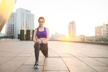 Portrait of a young sports girl squatting against the background of the sunset. Girl in sports wear sports on the street. Sports training in the background of the sunrise. Sports concept.