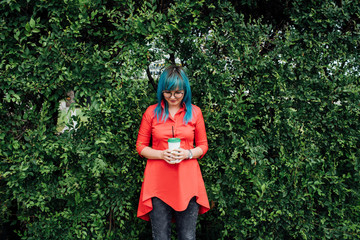 Young woman with dyed blue hair standing in front of a hedge with beverage