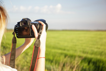 a photographer with a camera shoots a field and sky in a hot summer day