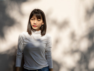 portrait of beautiful younger asian woman standing against white wall