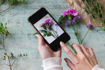 Woman's hands taking photo of flowers with smartphone