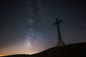 Italy, Marche, silhouette of summit cross on Monte Catria at night
