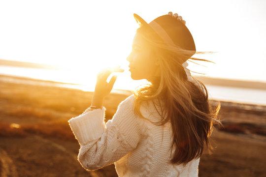 Beautiful young woman walking outdoors at the beach