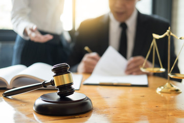 Business lawyer judge working about legal legislation Consultation with insurance  with gavel and balance for deciding on marriage divorce clients.
