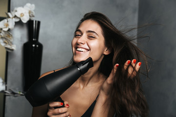 Photo of smiling woman with long dark hair and healthy skin drying her hair, while standing in bathroom