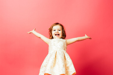 Portrait of an excited small toddler child with both arms out, isolated on pink studio background