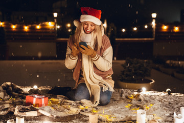 Emotional excited young woman sitting outdoors in evening in christmas hat using mobile phone.