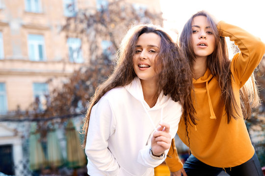 two young girls walking city having fun. joyful Women in bright colored hoodies walking, laughing and posing on the street