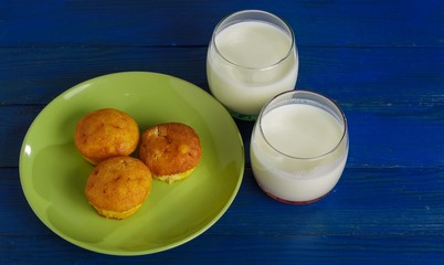 Cottage cheese cakes on a plate and two glasses of milk on the table.