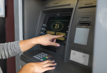 finance, cryptocurrency and technology concept - close up of woman at atm machine with bitcoin icon on screen