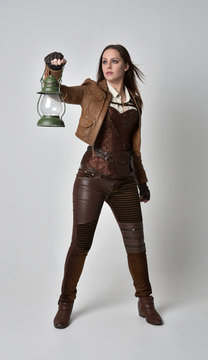 full length portrait of brunette  girl wearing brown leather steampunk outfit. standing pose, holding a gas lantern, on grey studio background.