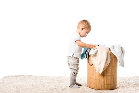 toddler boy standing in front of wicker laundry basket on carpet isolated on white