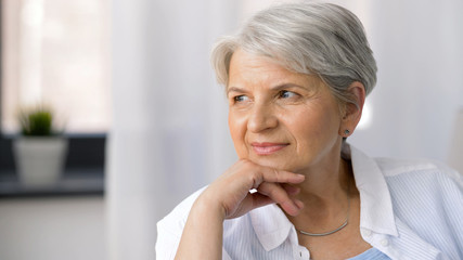 age and people concept - portrait of pensive senior woman