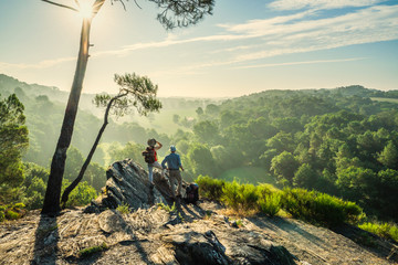 Hiker couple walk on a mountain trail, overlooking the valley. Wall mural