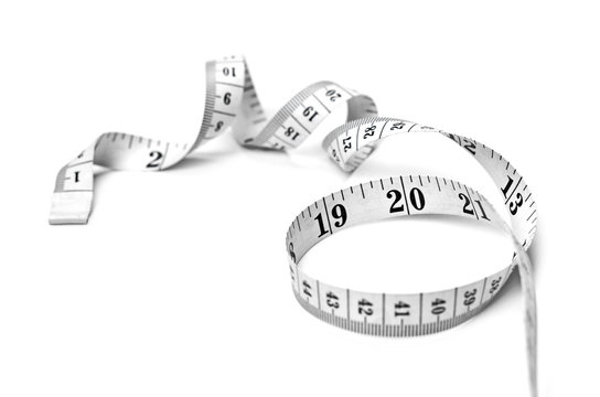 Curly measure tape, dieting or weight loss theme, isolated on white background. Black and white measure tape, top view.