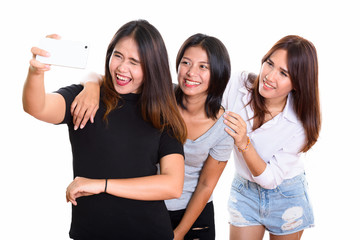 Studio shot of three happy young Asian woman friends smiling whi