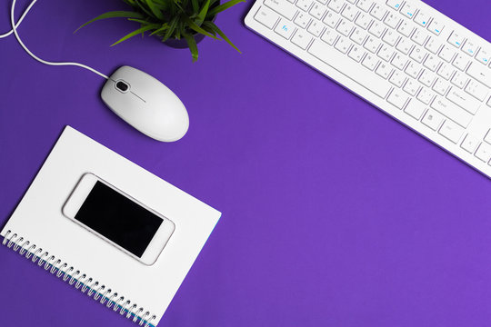 White computer keyboard on a bright purple paper background