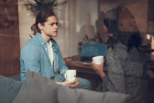 Serious conversation. Concentrated young man sitting with a cup of tea and frowning while listening attentively to his girlfriend and looking at her