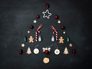 Christmas tree shaped out of different Christmas deco items, on black chalkboard