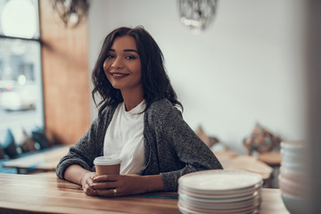 Waist up of beautiful smiling lady sitting at the bar counter and looking at you while touching her cup of coffee