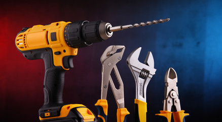 hardware tools including cordless drill and monkey spanner