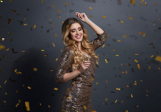 Woman drinking champagne and dancing under shower of confetti