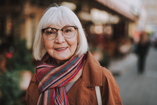 Portrait of stylish old lady in coat looking at camera and smiling. Street on blurred background