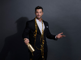 Man holding a bottle of champagne and pointing at copy space