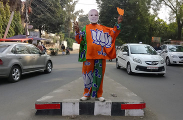 A supporter of India's Bharatiya Janata Party (BJP) wears a mask depicting the Indian Prime Minister Narendra Modi, and drapes himself with flags of BJP's symbol at a traffic signal in Bhopal