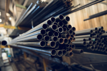 Industrial metal piping in a cold hard industrial factory setting. Metal iron cut pipes being prepared for scaffolding manufacture.