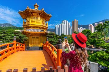 Woman take a photo at Golden Pavilion in Nan Lian Garden near Chi Lin Nunnery temple, Hong Kong.