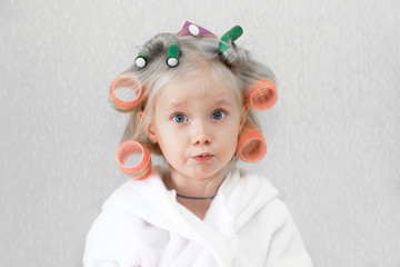 Girl with curlers hairpins in her hair. A little girl in a white coat spun pink curlers into her hair.