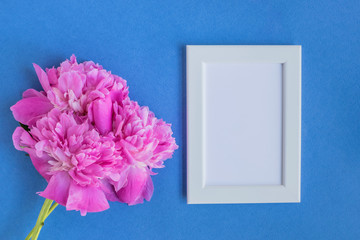 Mockup with a white frame and pink peonies