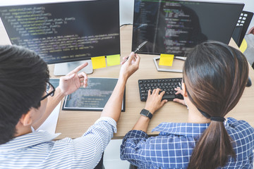 Two professional programmers cooperating at Developing programming and website working in a software develop company office, writing codes and typing data code