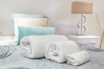 Rolls of towels symmetrically on the bed in the bedroom.