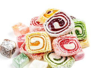 Candy background isolated on white background. Colored candy wrapped in a roll and sprinkled with coconut flake. Turkish delight.