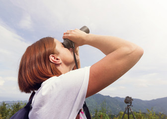 Girl with red hair watches in the binoculars birds against the background of mountains. Observation of birds. Birdwatching