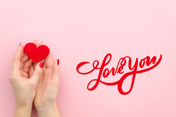 Love You hand lettering. woman hans holds red heart on a pink background Top view flat lay trendy