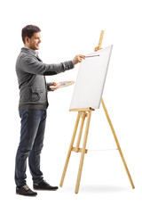 Smiling young man painting on a canvas