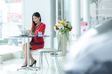 Asian smiling successful businesswoman in suit talking on phone using tablet sitting at office workplace, young entrepreneur making answering call consulting client speaking by cell.